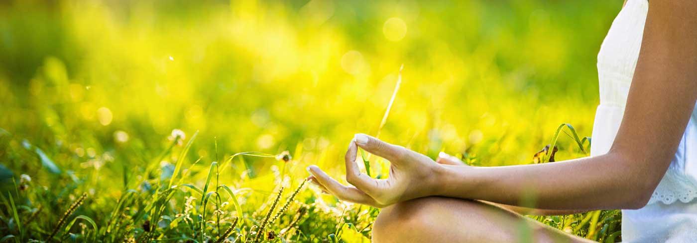 Meditation mit Handmudra auf der Wiese