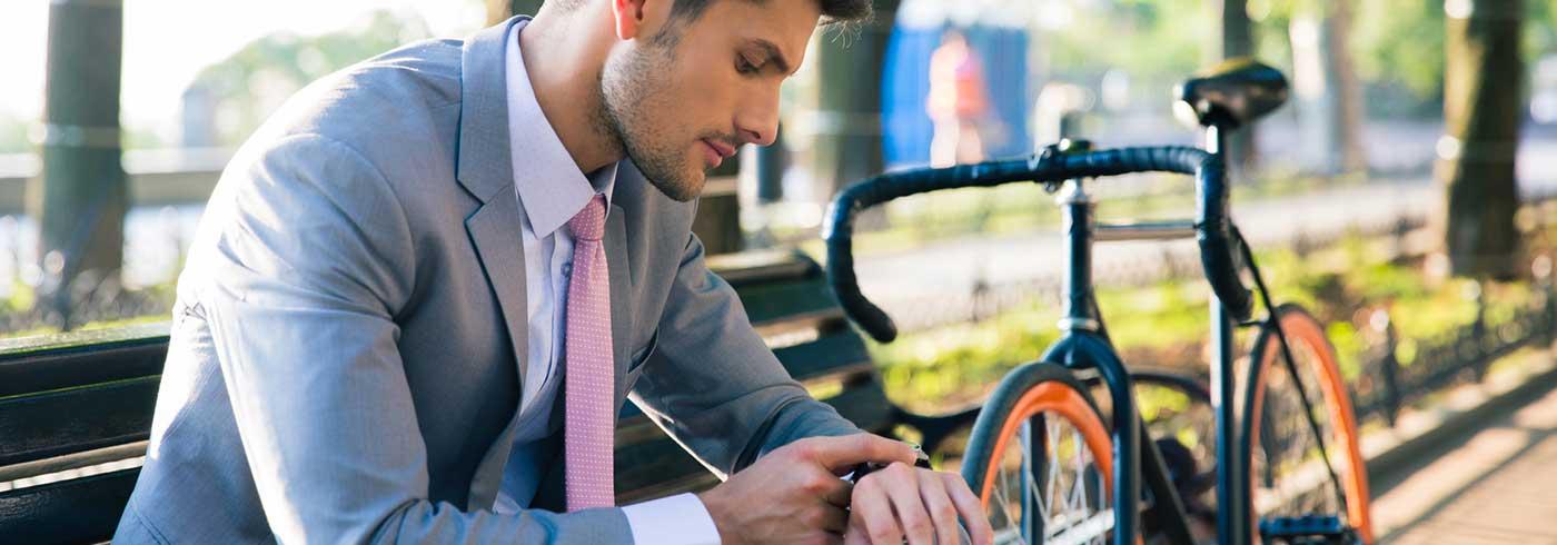 Unternehmer macht Pause auf einer Bank und schaut auf die Uhr