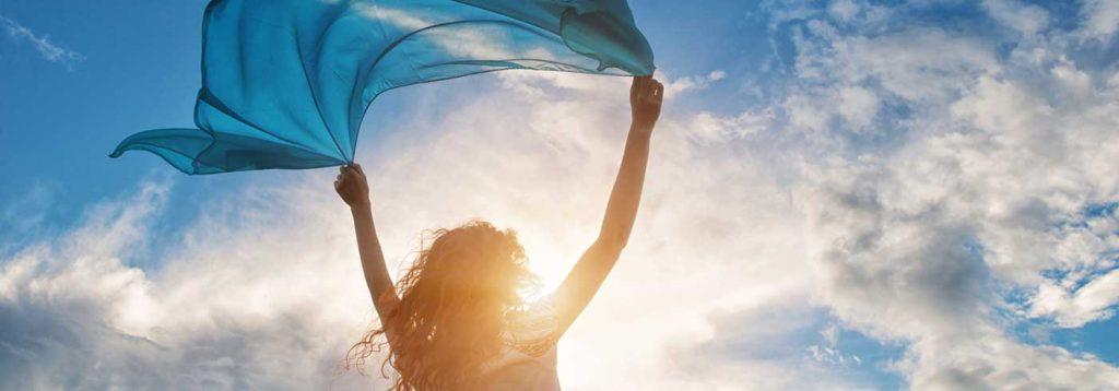 Frau fühlt den Wind bei Sonnenschein