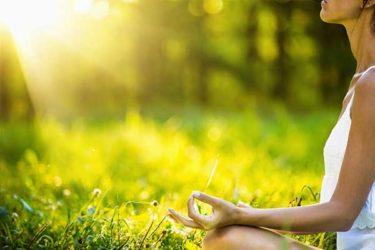 Frau meditiert auf einer Wiese