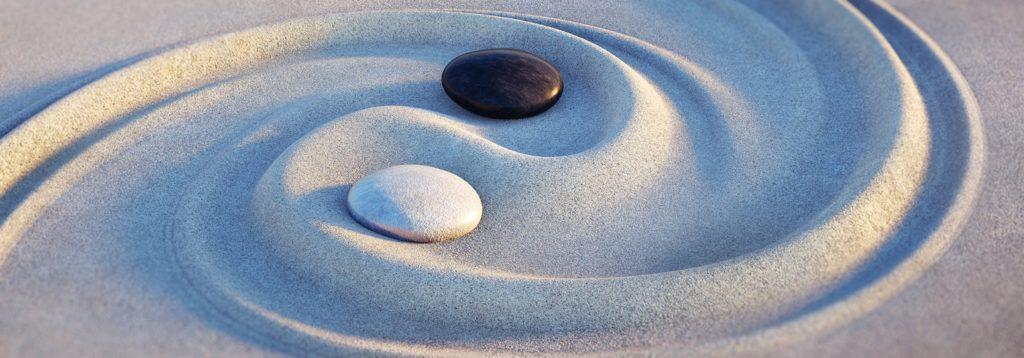Yin und Yang Steine im Sand